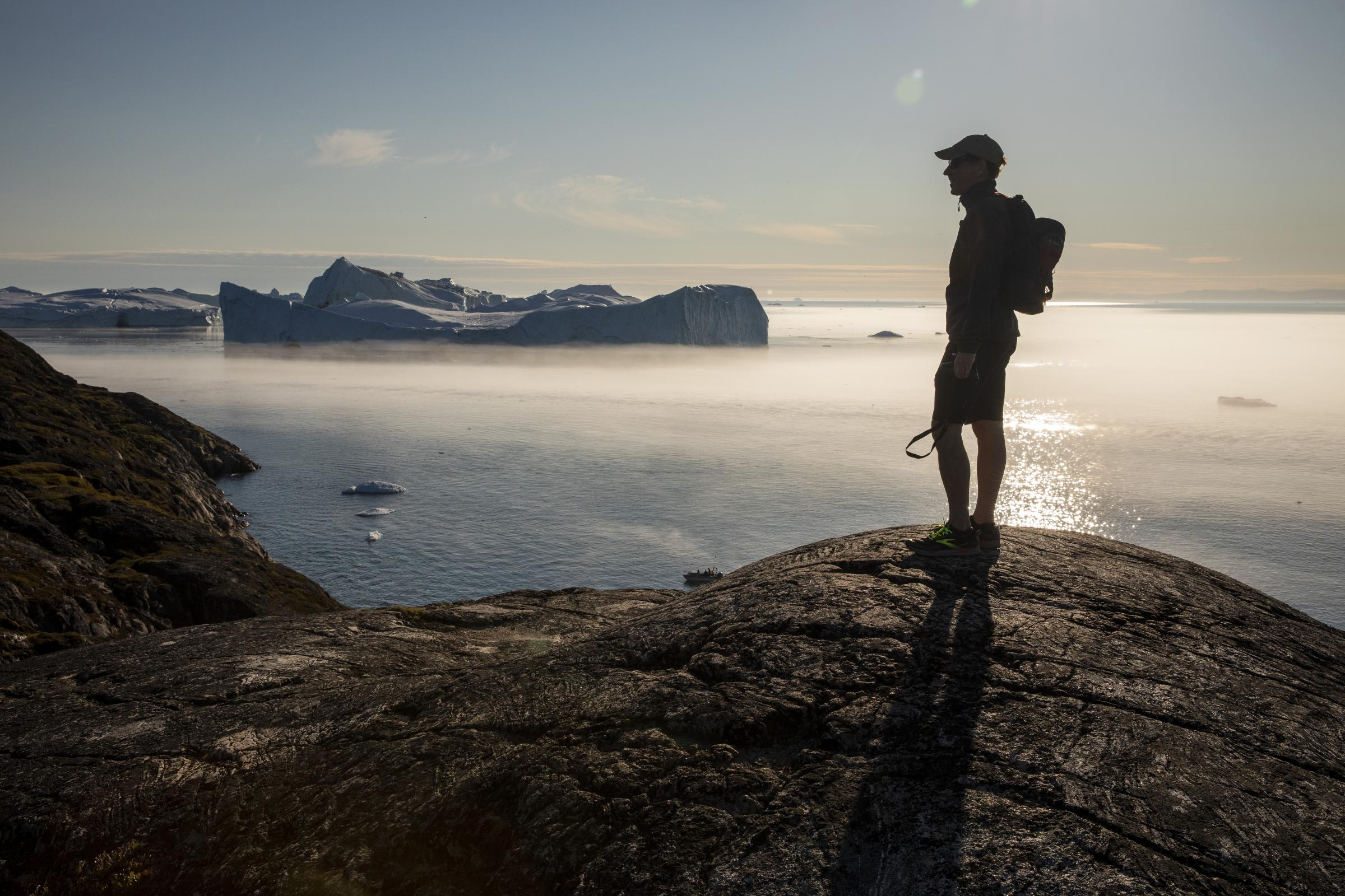 silhoutted man stands amid water and icebergs
