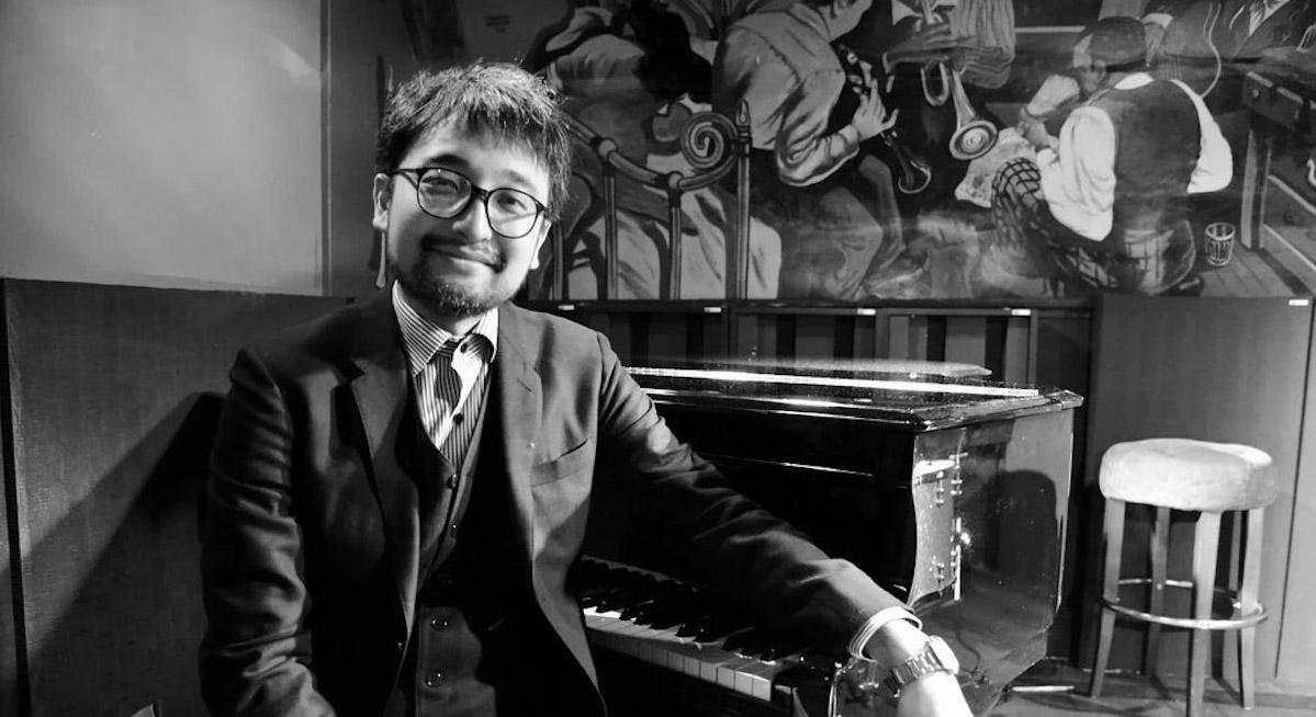 Jazz pianist Tadataka Unno sitting in suit