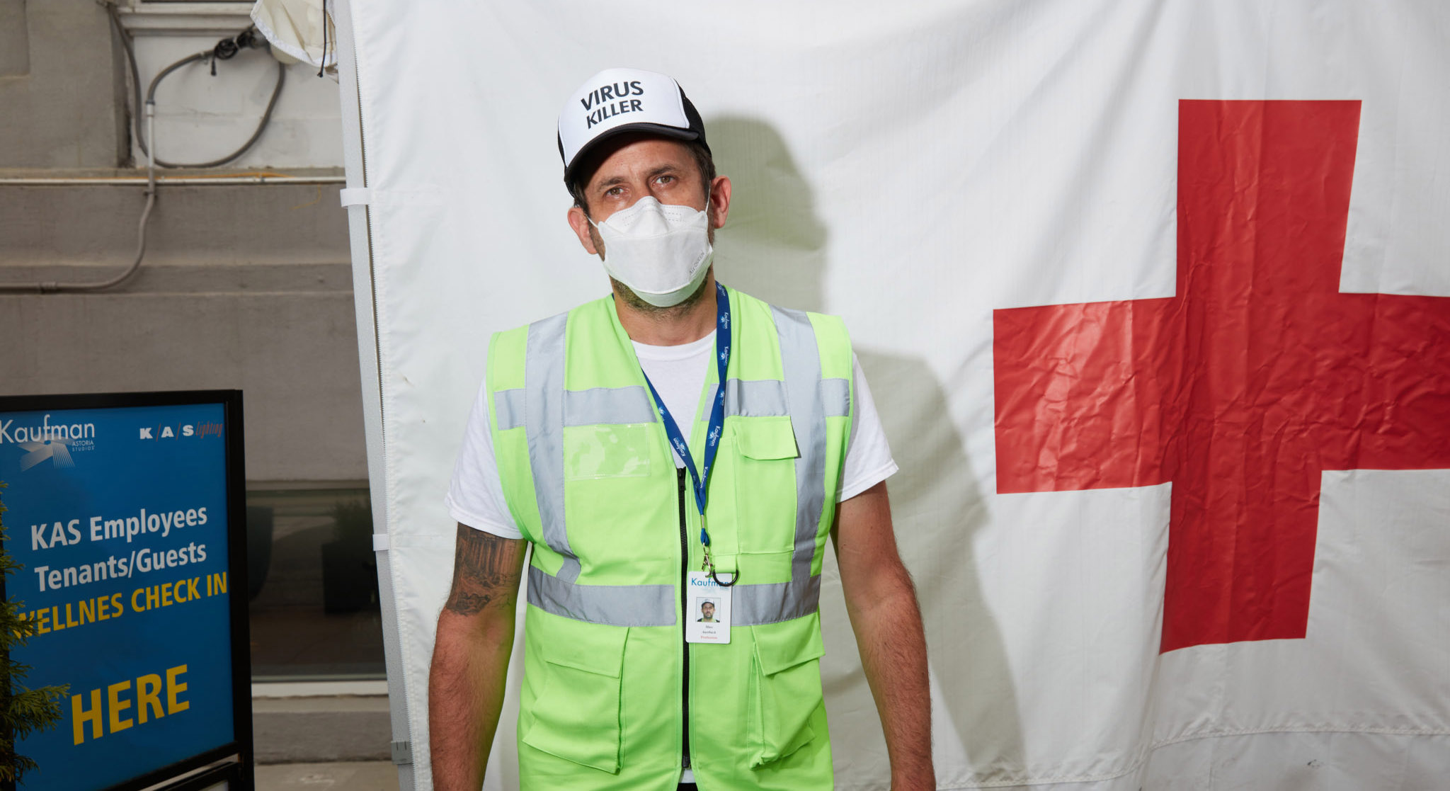 "Man in facial mask, hat reading ""Virus Killer"" and safety vest stands in front of large red cross"