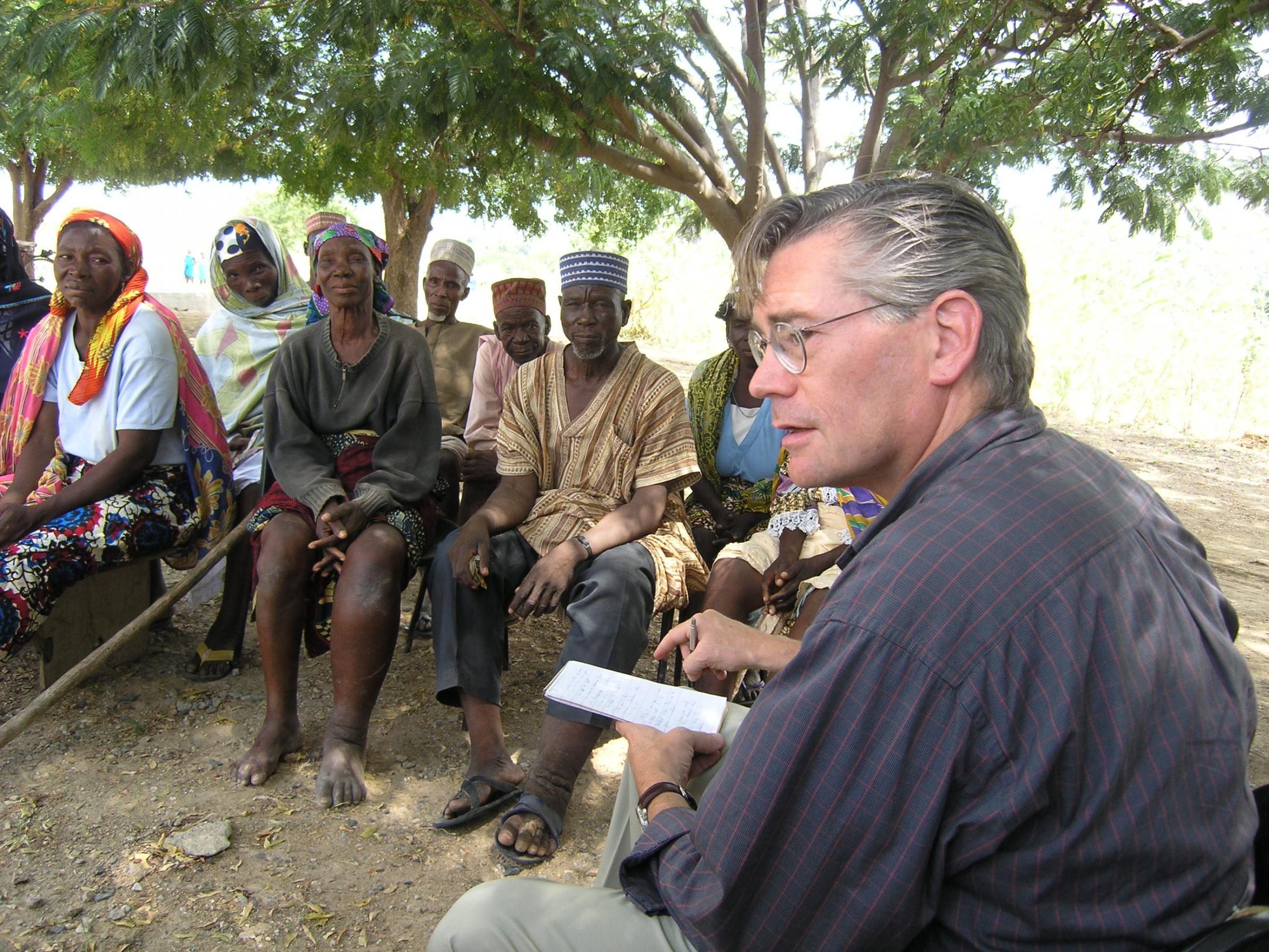 McNeil in foreground outdoors; several Nigerian men and women on bench across from him