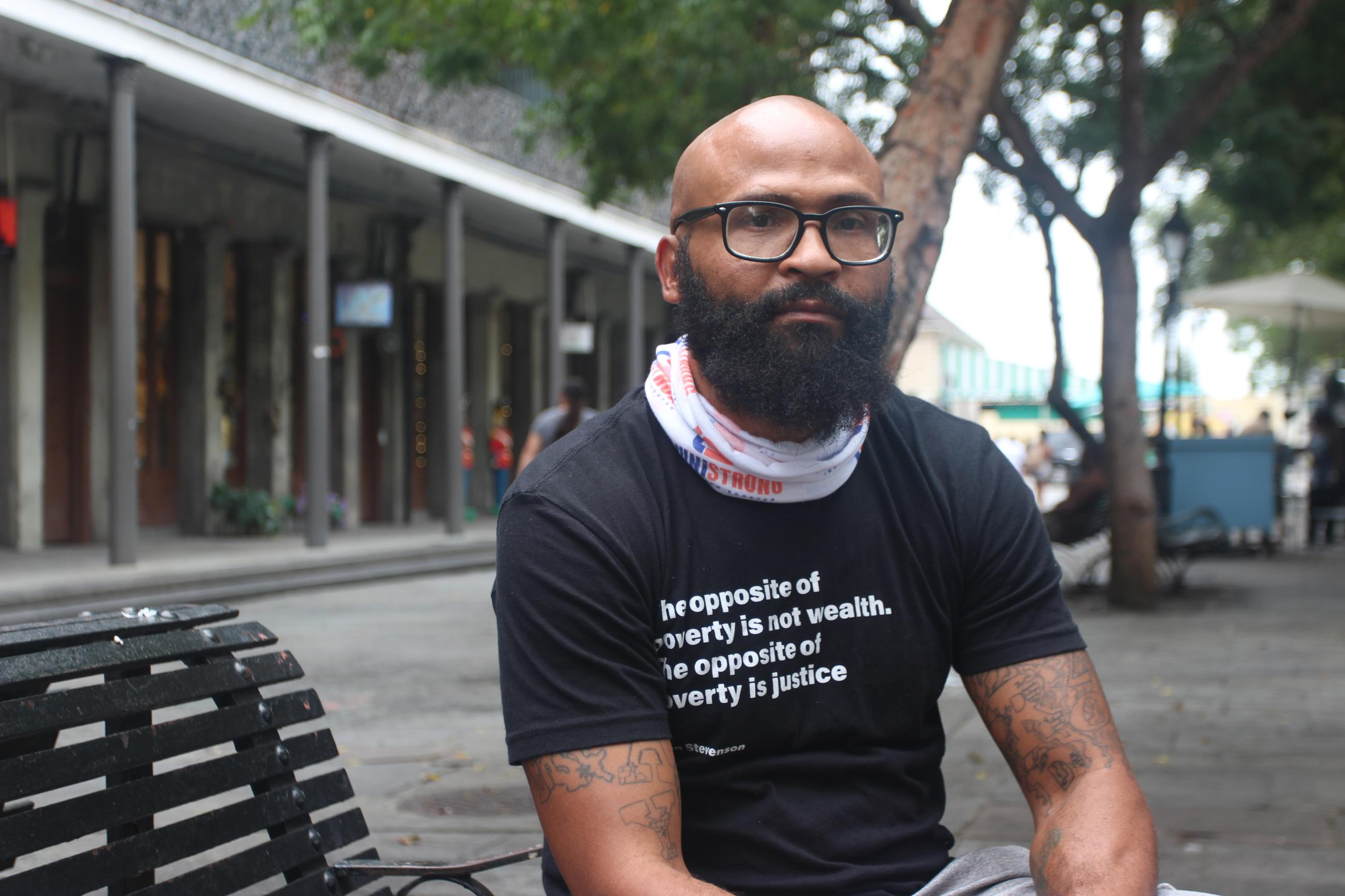 """Man with beard, glasses and black t-shirt reading """"The opposite of poverty is not wealth. The opposite of poverty is justice"""" sits on bench with trees behind him."""