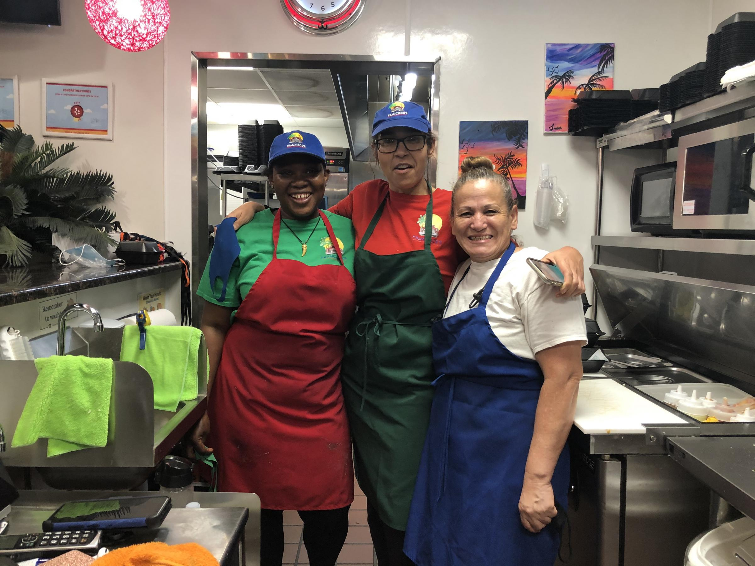 three women in aprons and hats in restaurant kitchen