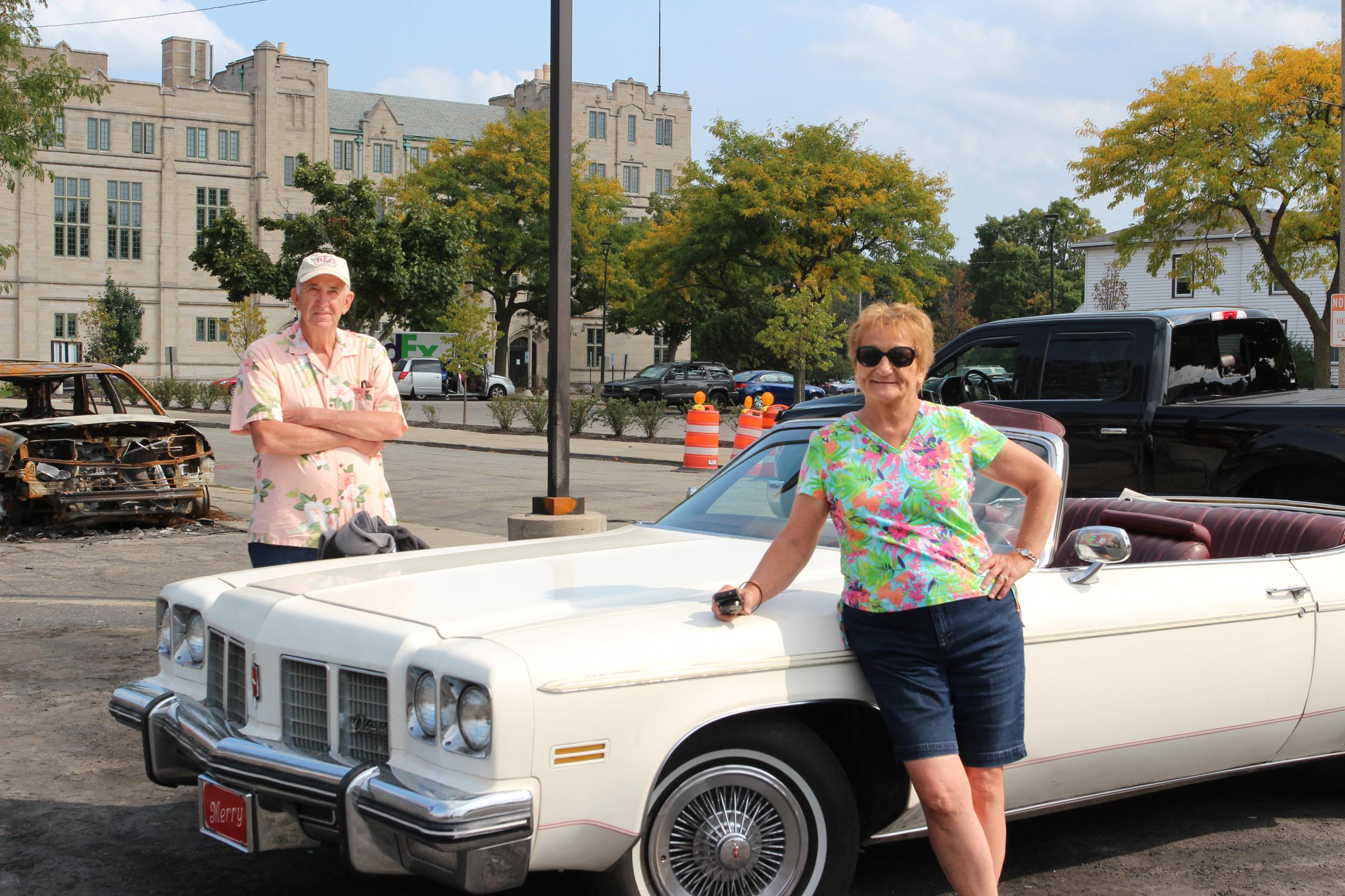 older man crosses arms behind classic car while an older woman smiles in front of it