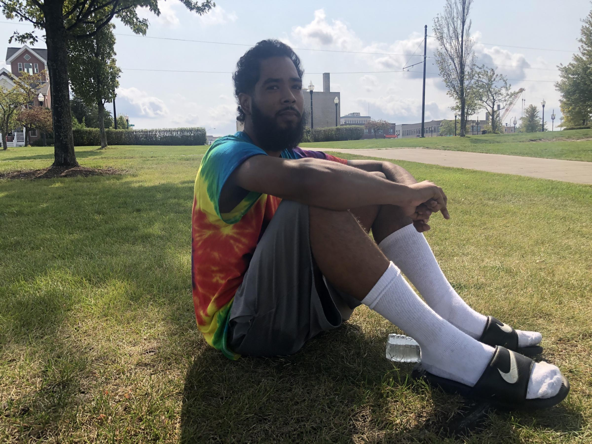 Young, bearded man in tie-dye shirt sits on grass