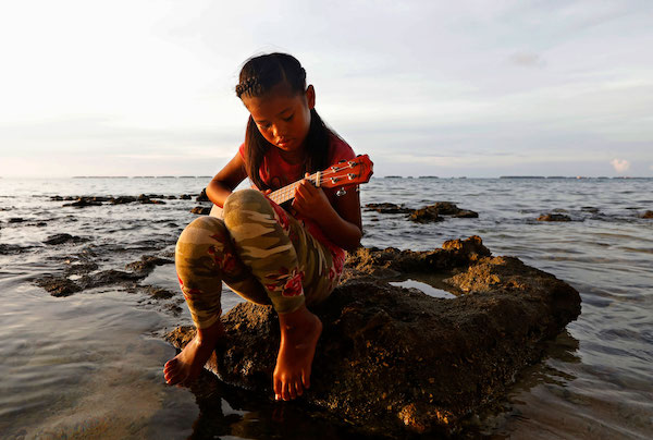 Marshallese girl playing instrument