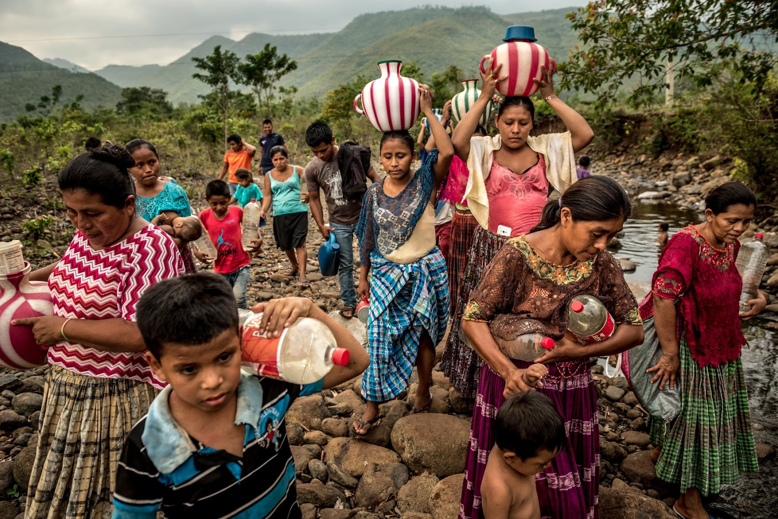 A group of women and children carry jugs and 2-liter soda bottles of water in a lush and mountainous landscape