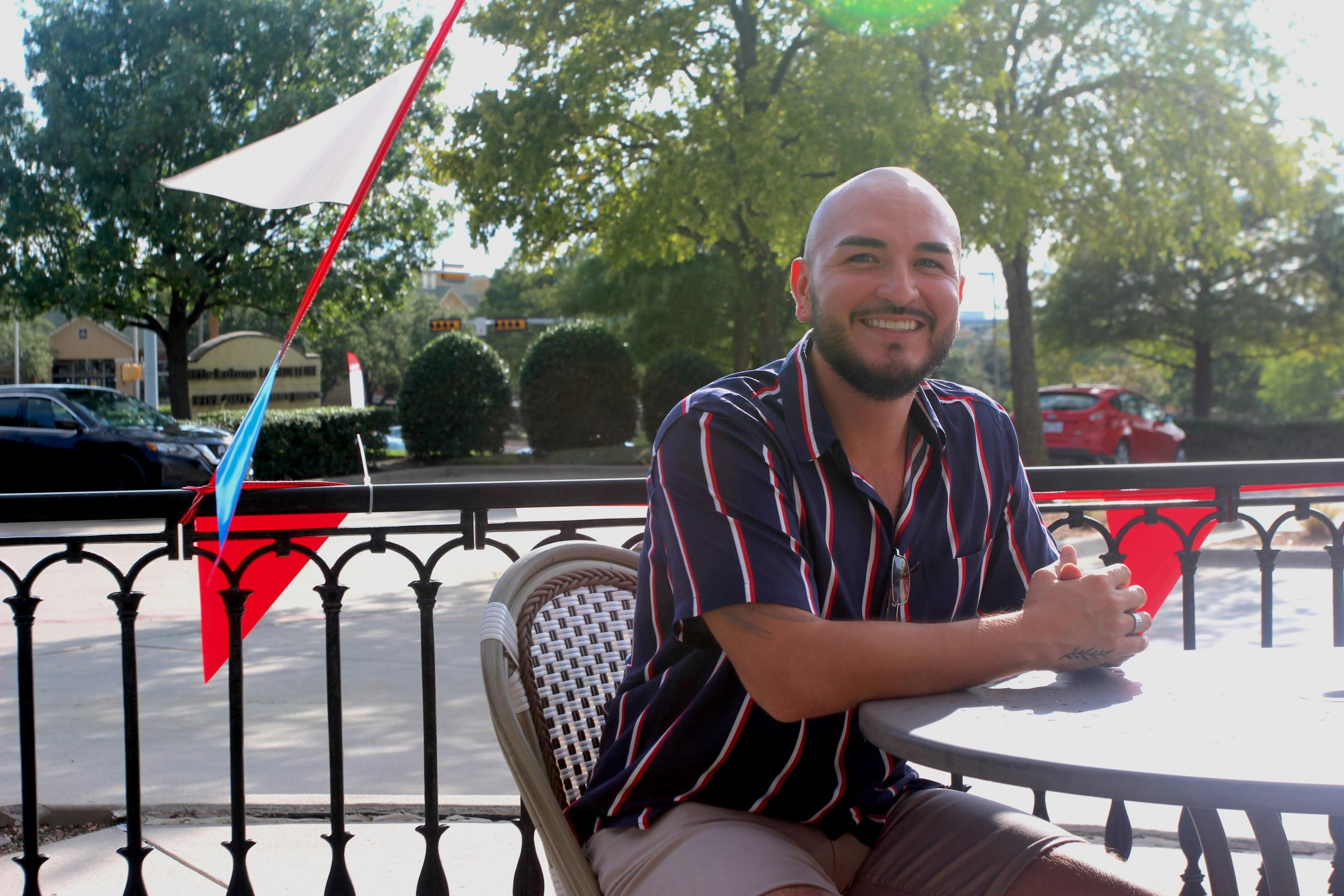 man sits at table outdoors in the sun