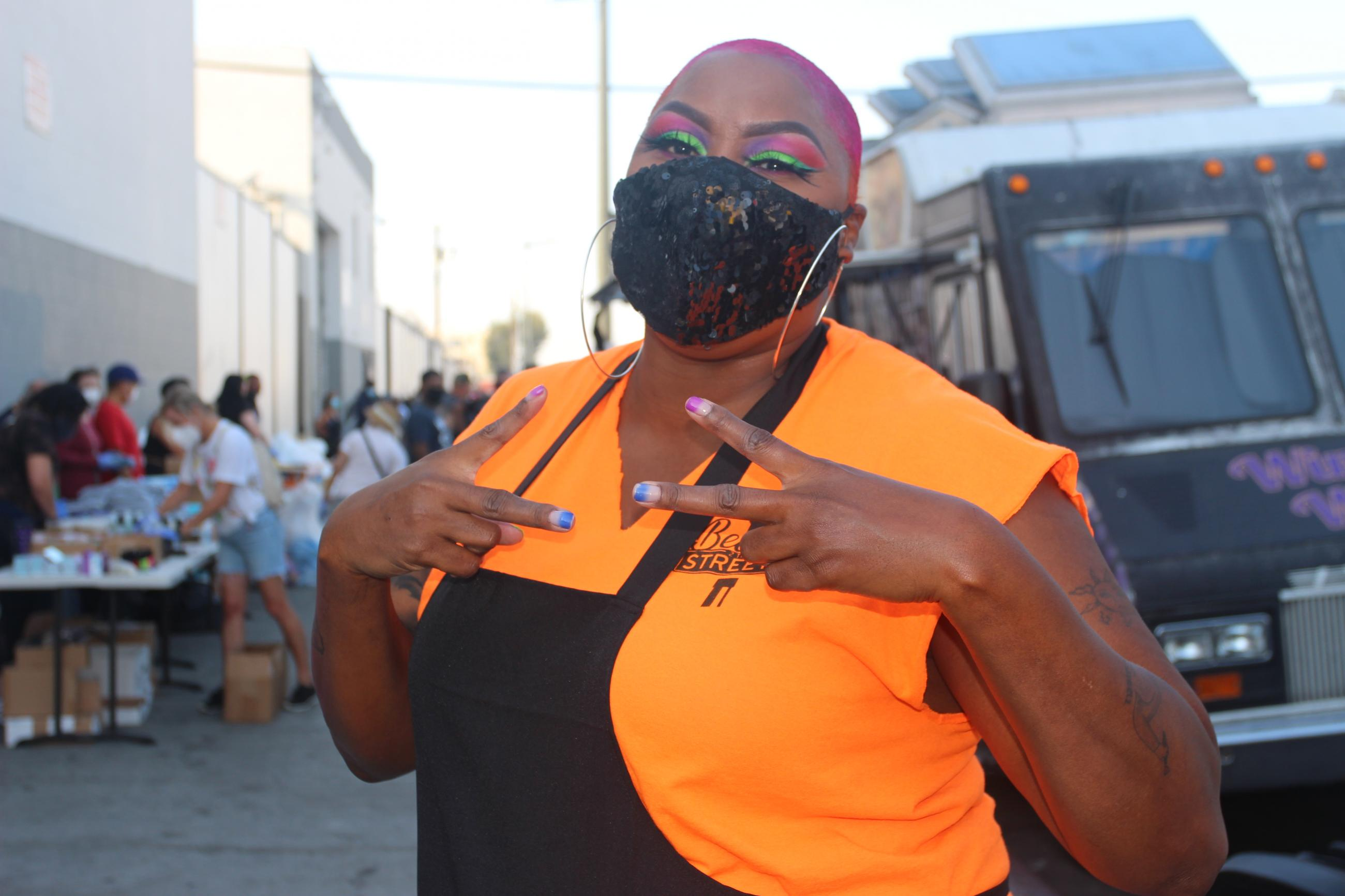 Woman with black sequin mask, vibrant eye green and magenta shadow and matching hair holds fingers in peace signs against her orange shirt and black apron