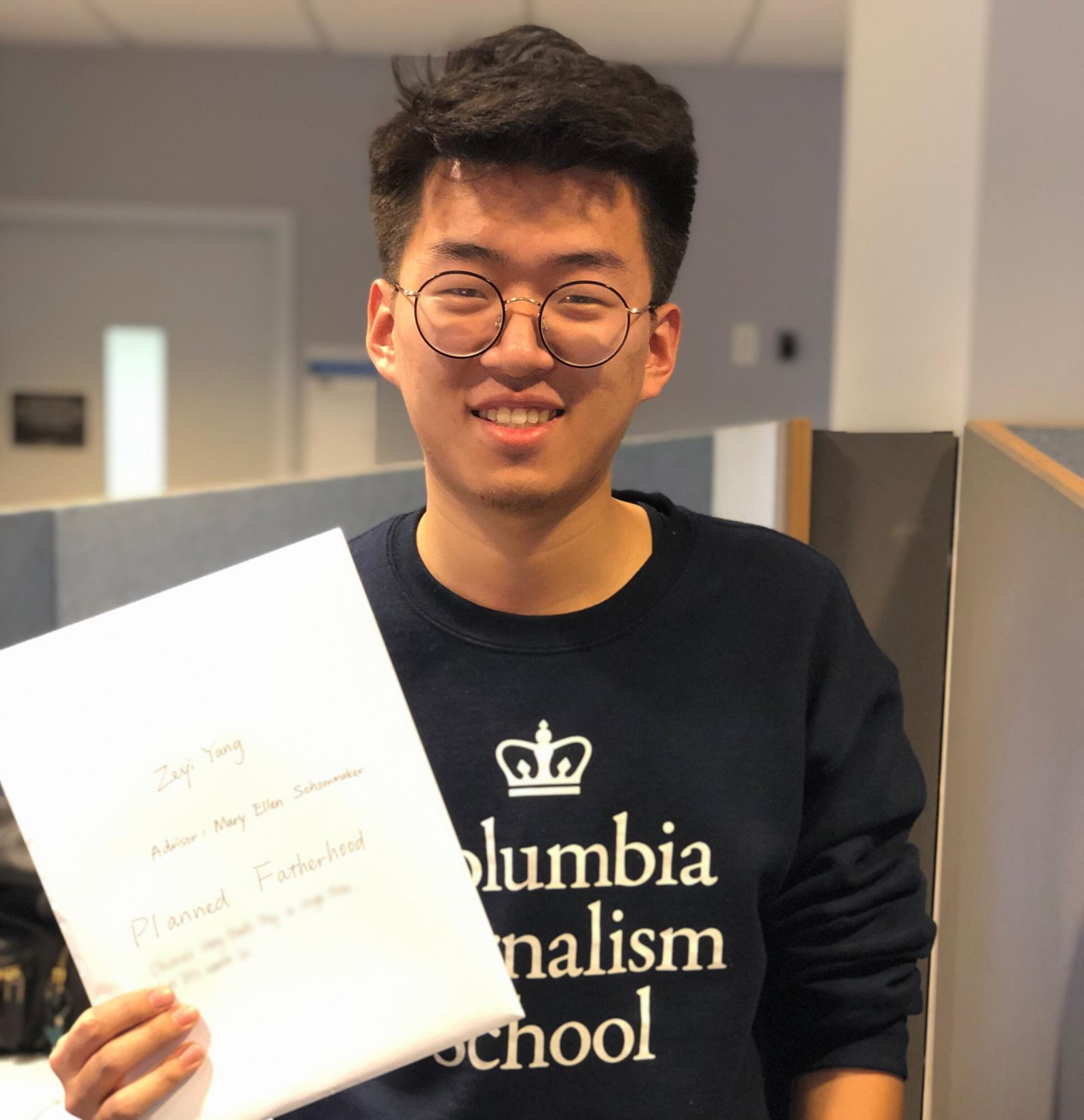 Zeyi Yang holding printed thesis