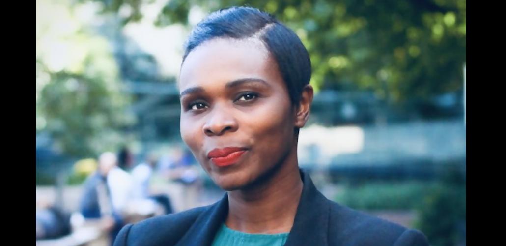 Rita Omokha, wearing blue blazer and standing outdoors