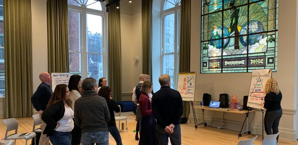 Fellows work together in front of stained glass window in Pulitzer's World Room