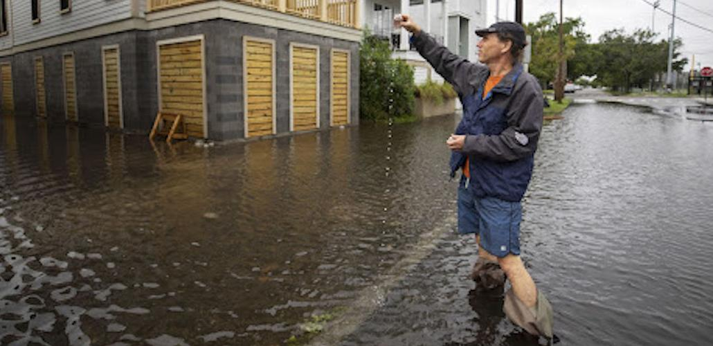 man stands in ankle deep waters outside building