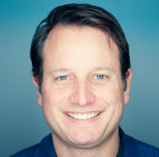 Headshot: Corey Ford on blue background