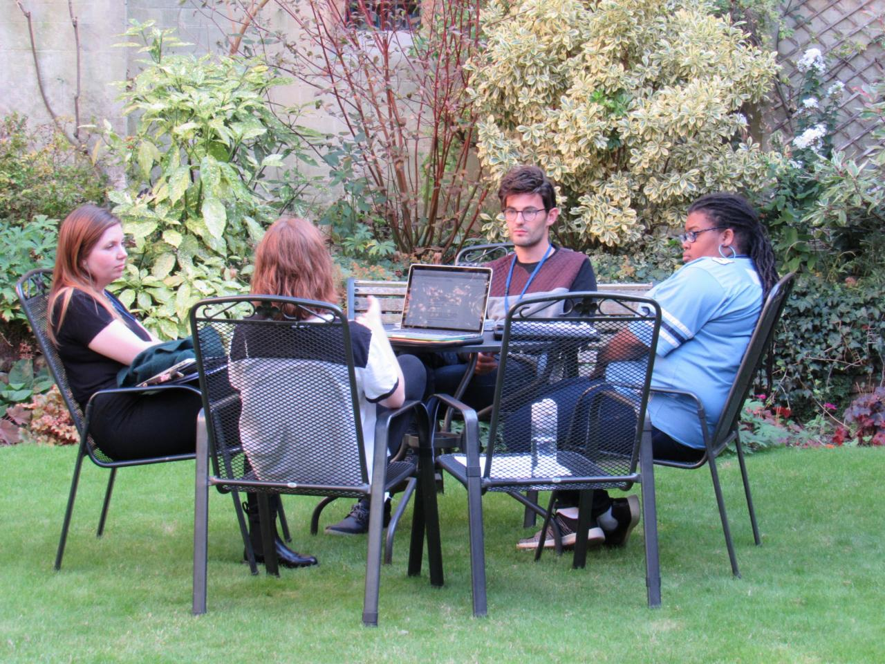 Four students sitting outside at patio table with laptop