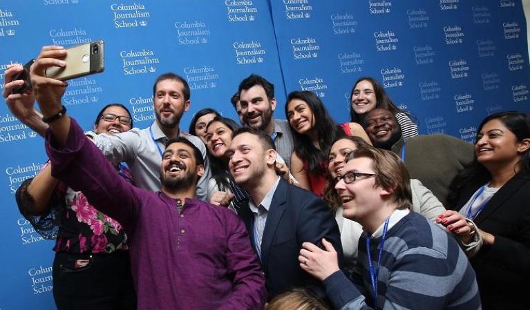 group of alumni taking selfie against blue J-School backdrop