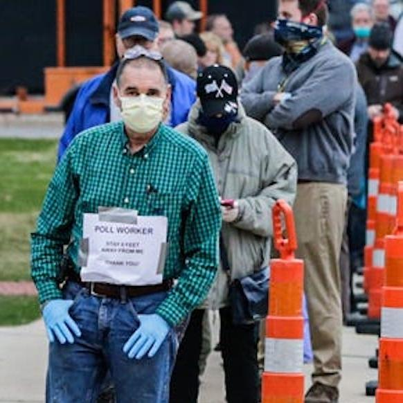 masked pollworker in front of outdoor line of voters