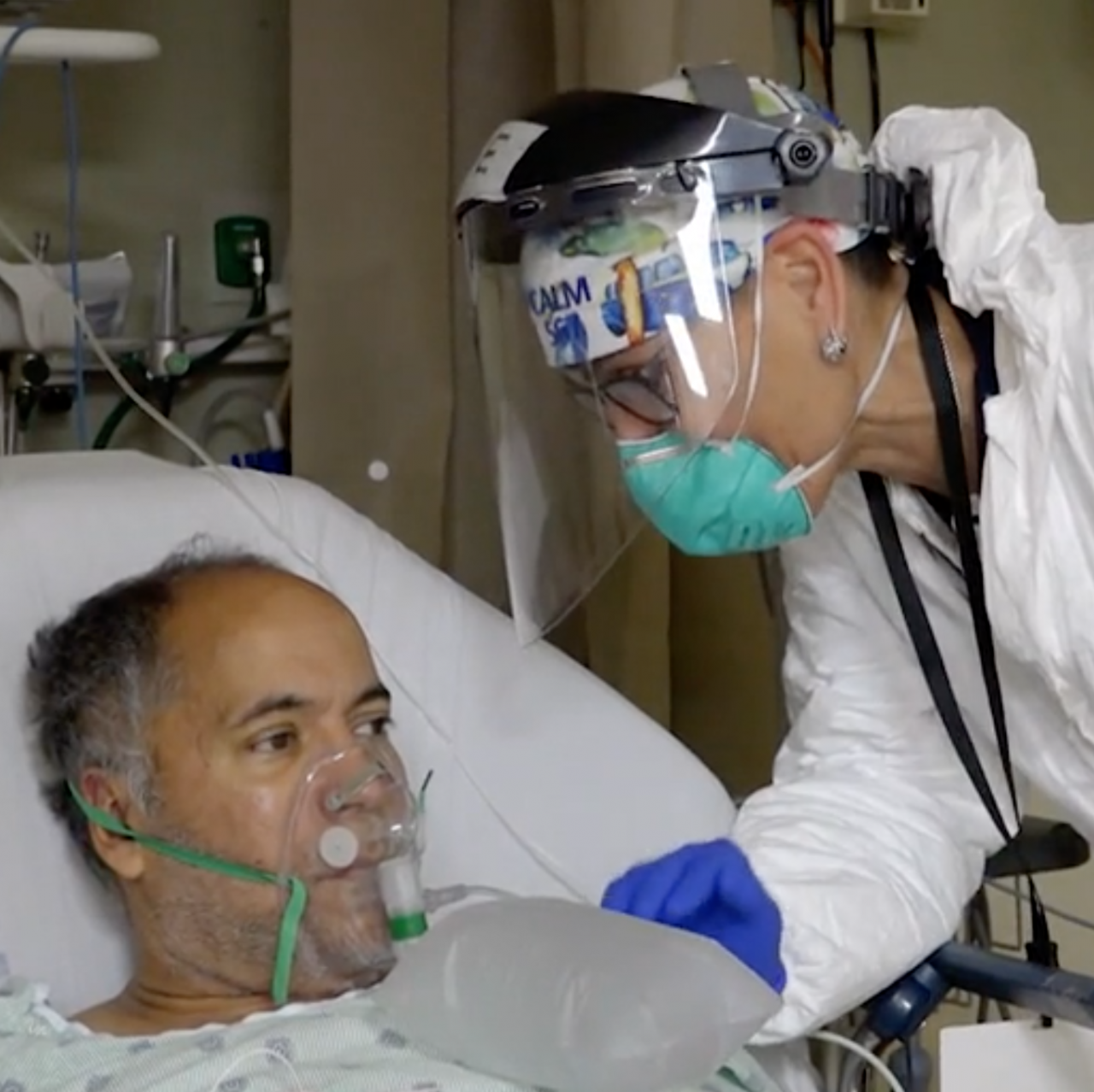 doctor in face shield leans over man with respirator