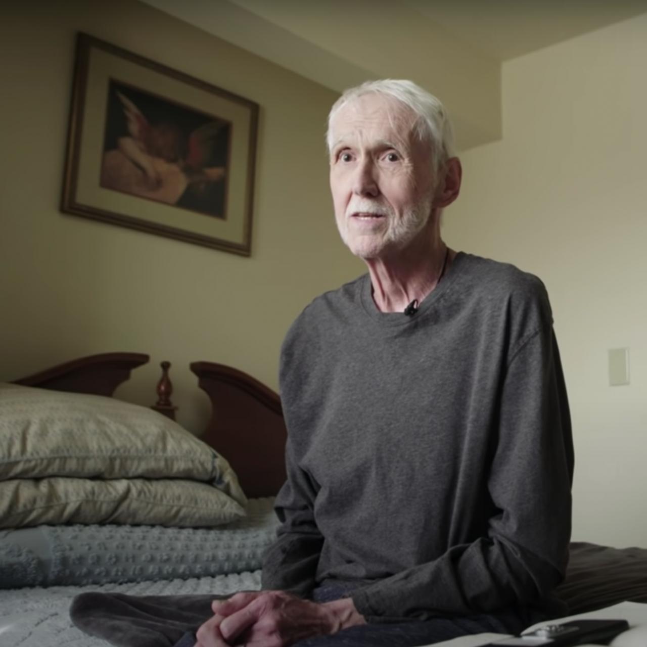 older man sitting on bed
