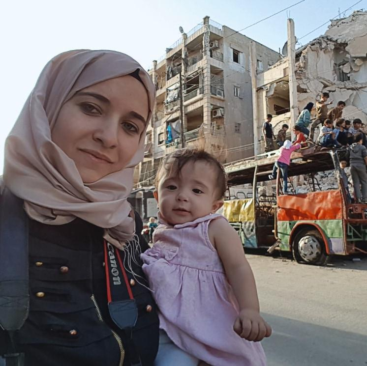 woman and baby in front of wreckage