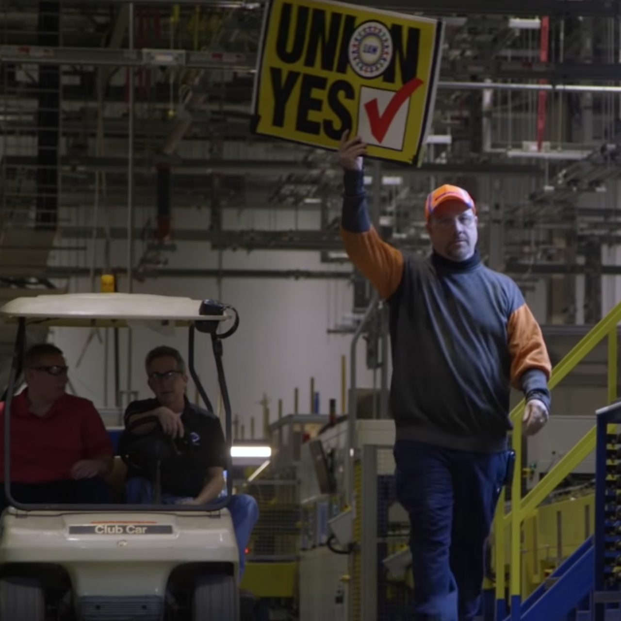 man holding Union Yes sign in factory