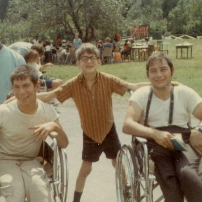vintage photo of two young men in wheelchairs with a boy standing between them