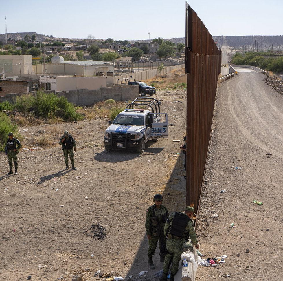 end of large wall in arid landscape and uniformed men