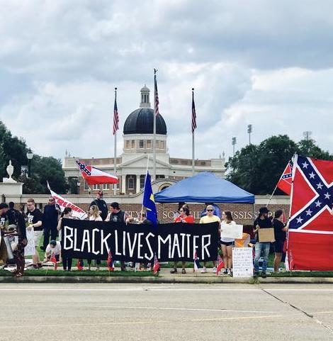 outdoors, people holding Black Lives Matter banner near large confederate flag