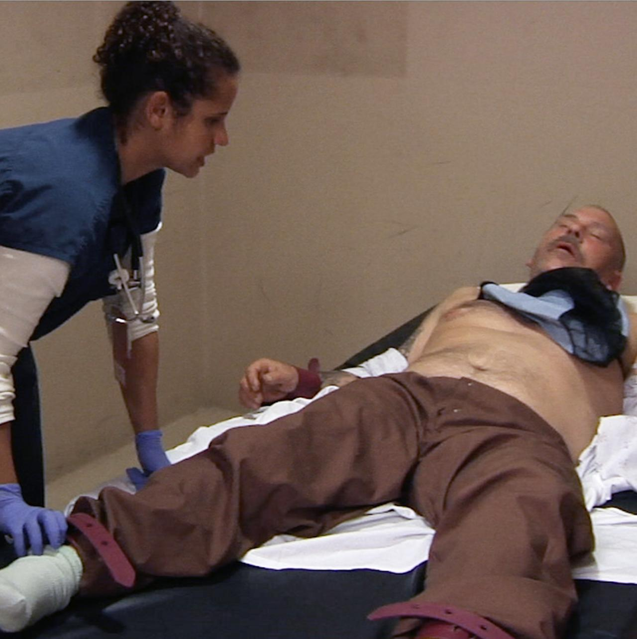 female medical professional stands over prone male patient