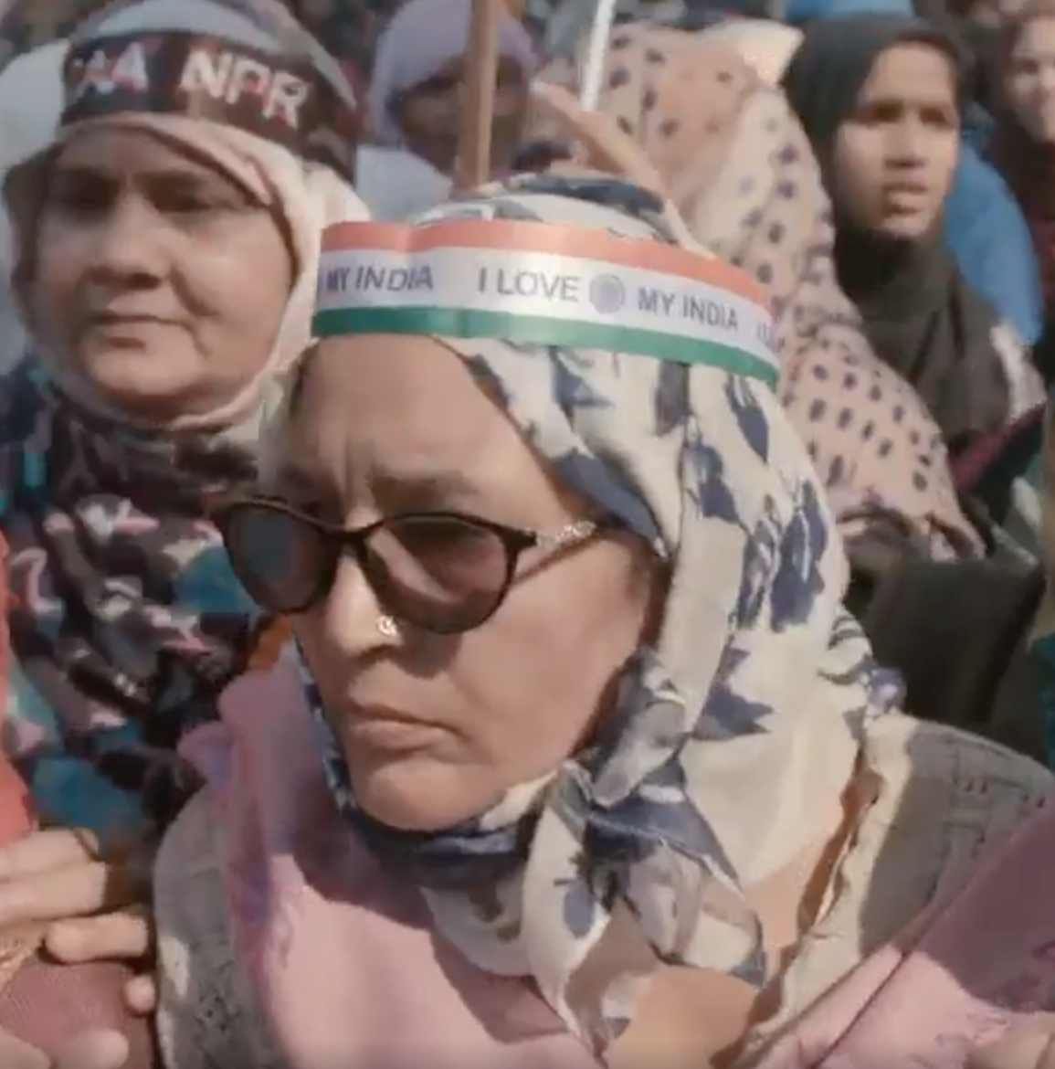 """woman in headcovering wearing band around head reading """"I love My India"""""""