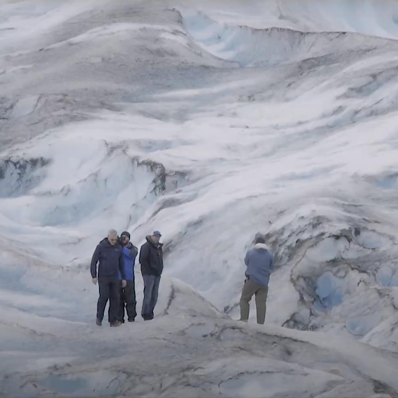 four people in coats walking on snowy, rocky terrain