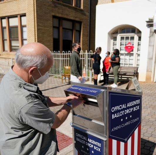 man in mask inserting ballot into drop box