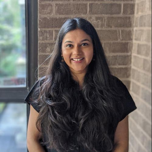 Indrani Basu in front of brick wall and window