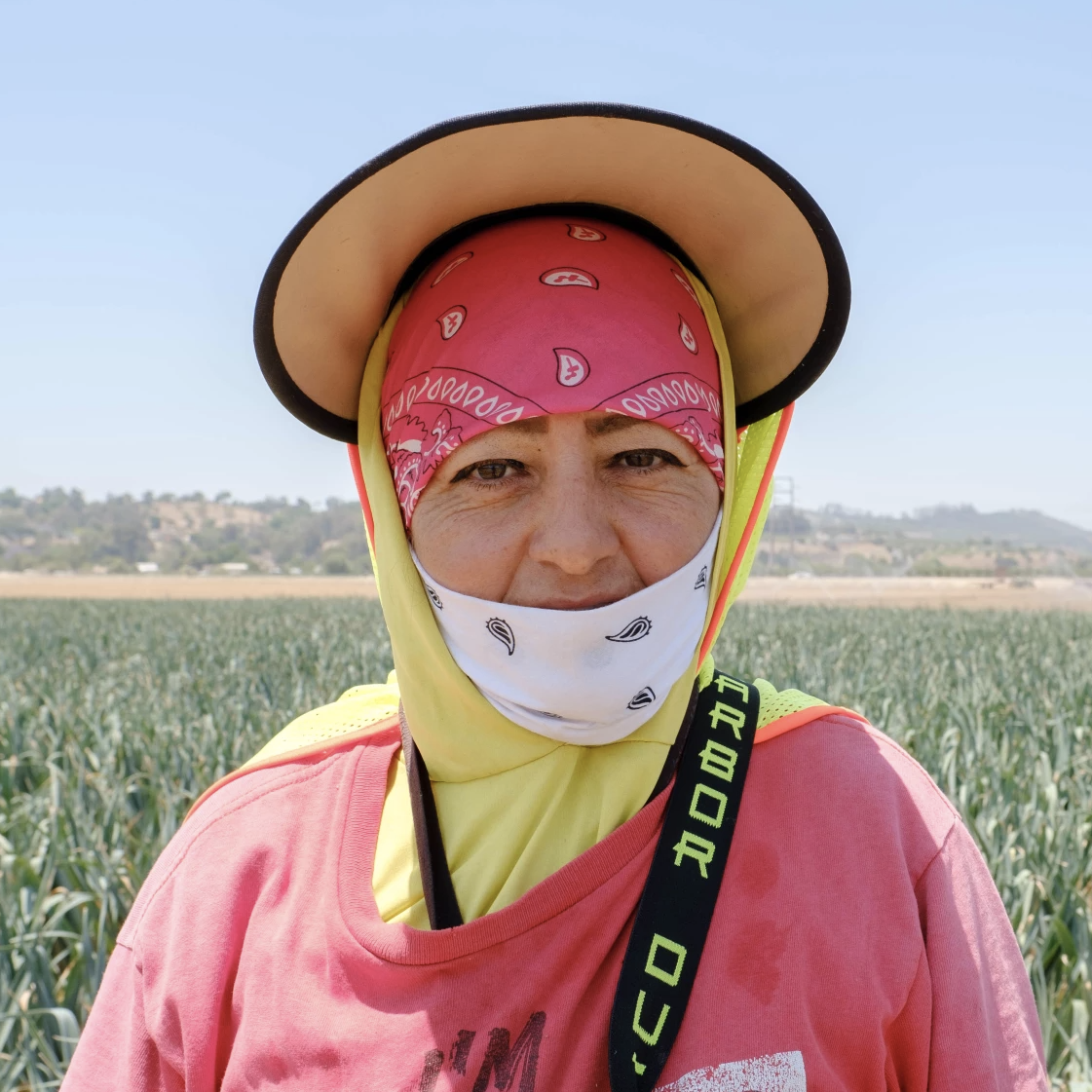 woman in hat and bandana facial mask stands in field