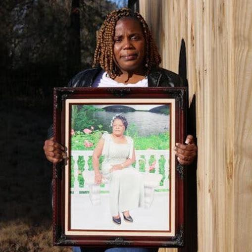woman holds framed portrait of another woman