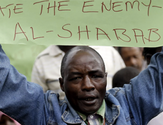 man holding sign; words visible include 'the enemy  al-shabab'