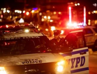 Police car and officer; image via New York Times story