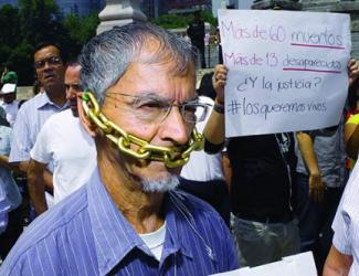 Protest with Spanish sign; in foreground: Man with chain prop around mouth