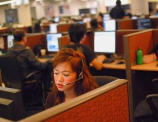 Woman in cubicle wearing headset: Image via Vox story