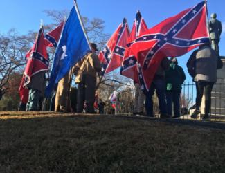 people standing outside fence while holding Confederate flags
