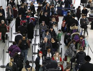 travelers waiting in airport lines with luggage