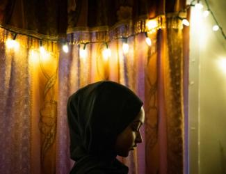 woman in headcovering in front of curtain and lights