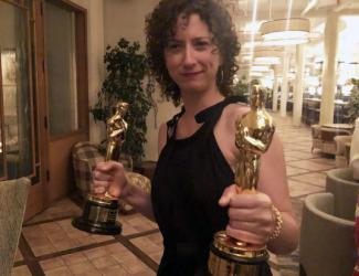 Jessica Bruder wears black dress and holds two Oscar statuettes