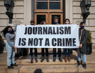 """Masked students hold sign reading """"Journalism is Not a Crime"""" on steps of Pulitzer Hall"""