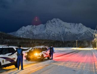 Two police cars in front of snowy mountain